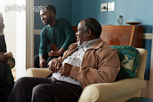 Smiling senior man looking at male friends talking while sitting in living room during Christmas festival - gettyimageskorea