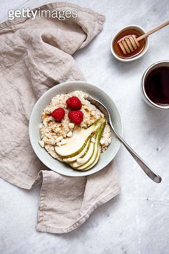 oatmeal with raspberries and pear in a rustic plate on a marble table. Morning concept with copy space - gettyimageskorea