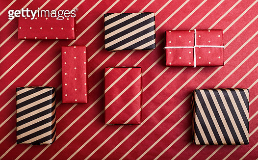Boxes wrapped in polka dot and striped paper on red craft paper. Camouflage, invisible and safety savings - gettyimageskorea