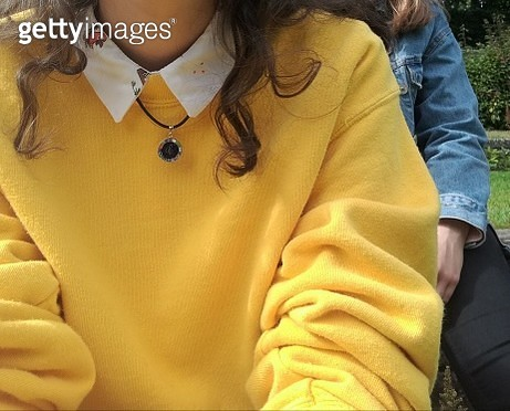 Midsection Of Woman In Yellow Sweater Sitting With Friend - gettyimageskorea