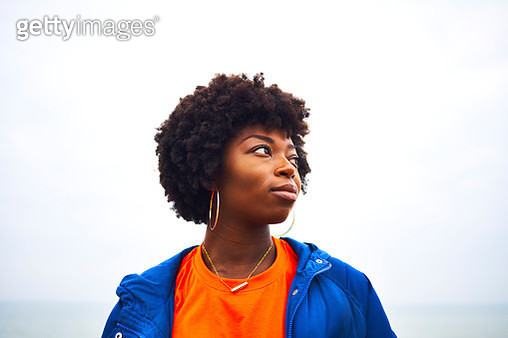portrait of woman looking off camera with colourful clothing - gettyimageskorea