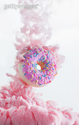 Colorful pink cloud around a sweet donut with sprinkles. Dissolving paint on a white background with copy space - gettyimageskorea
