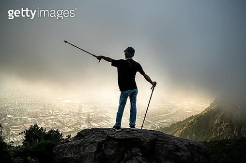 An outdoor mountaineering man pointing his hand at the distance in the mountains - gettyimageskorea
