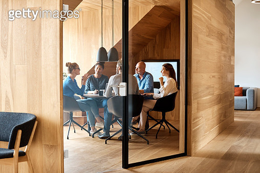 Business professionals discussing in meeting seen through glass door at office - gettyimageskorea