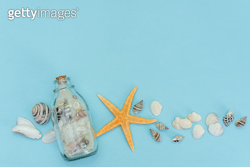Summer side border of sand, sea shells and star fish on blue wooden background - gettyimageskorea