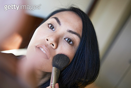High angle close-up of woman applying blusher on face at home - gettyimageskorea