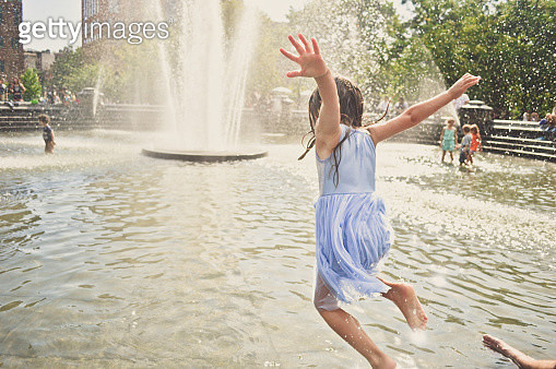 A girl jumping into the water at a New York city fountain on a hot summer day. - gettyimageskorea