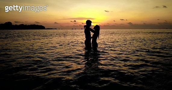 Silhouette Couple Standing In Sea Against Sky During Sunset - gettyimageskorea