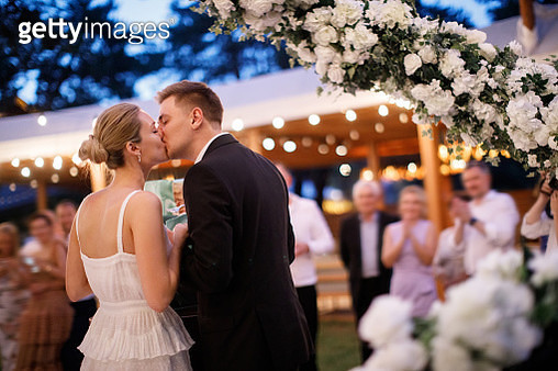 Beautiful couple is kissing at the celebration - gettyimageskorea