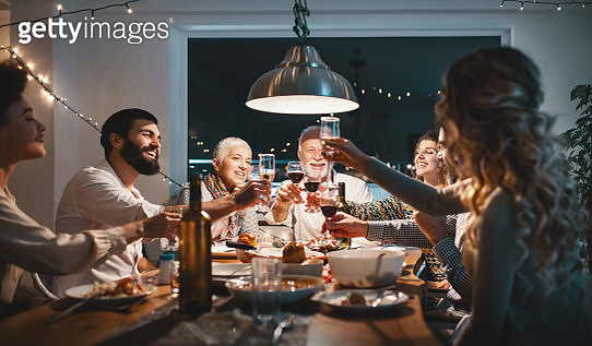 Closeup side view of a family having a Christmas eve dinner. They are having some traditional roast, gravy and vegetables and also some vegetarian food. There are three men and four women at the table having casual conversation. - gettyimageskorea