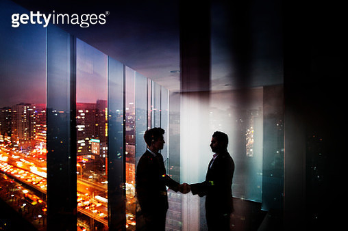 Businessmen shaking hands in office at night with city view - gettyimageskorea