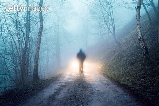 A silhouetted figure with car headlights behind. On a spooky forest track on a foggy winters evening - gettyimageskorea