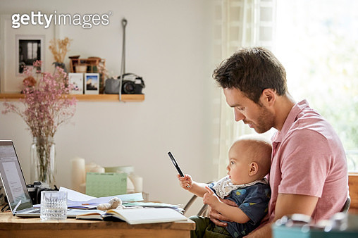 Man with laptop and papers looking at playful son - gettyimageskorea