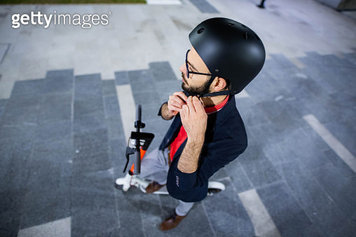 High angle view of man setting up his crash helmet for electric scooter ride - gettyimageskorea
