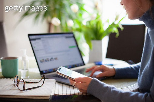Woman working from home using laptop computer while reading text message on mobile phone - gettyimageskorea