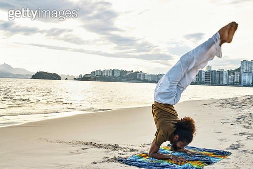 man doing yoga on the beach - gettyimageskorea