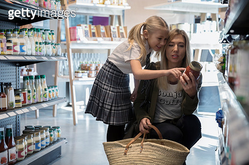 Mother and daughter in school uniform grocery shopping, reading label on can in market aisle - gettyimageskorea