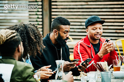 Friends exchanging contact information on smart phones during party at outdoor bar - gettyimageskorea