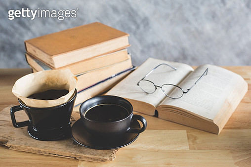 Close-Up Of Coffee By Books On Table - gettyimageskorea