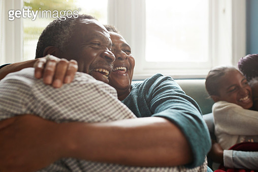 Romantic senior couple embracing on sofa at home - gettyimageskorea