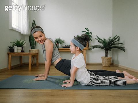 Mother doing on yoga mat with little daughter at home. - gettyimageskorea