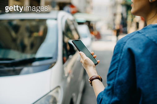Woman ordering a taxi ride with mobile app on smartphone in the city - gettyimageskorea
