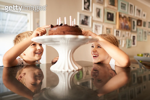 Shot of a siblings licking a birthday cake on kitchen counter - gettyimageskorea