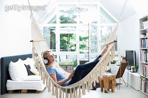 Relaxed woman at home lying in hammock listening to music - gettyimageskorea
