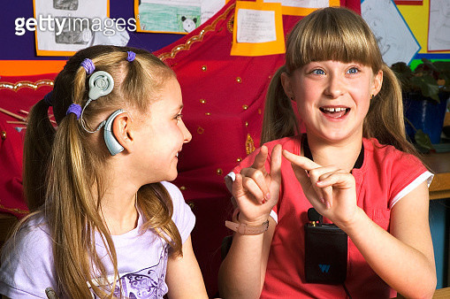 Deaf children with hearing aids in a school class room using sign language - gettyimageskorea