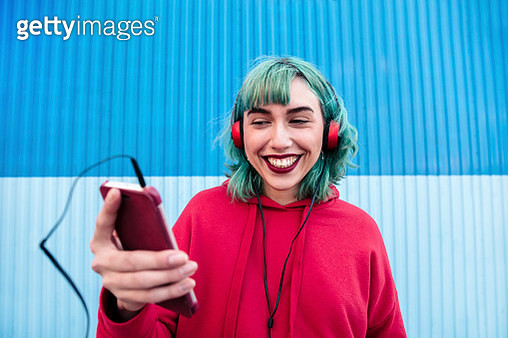 Portrait of laughing young woman with blue dyed hair with headphones taking selfie with smartphone - gettyimageskorea