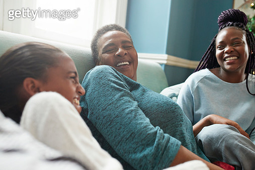 Grandmother relaxing with granddaughters on sofa - gettyimageskorea