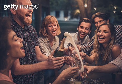 Young man splashing while opening champagne on a night party with his friend. - gettyimageskorea