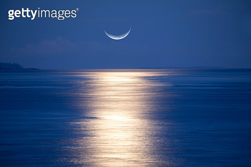 Crescent moon rising over sea - gettyimageskorea