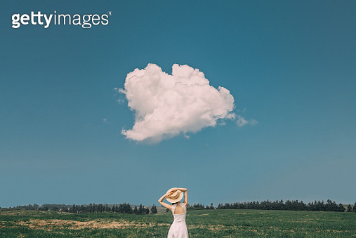 Young woman with a hat and cloud - gettyimageskorea