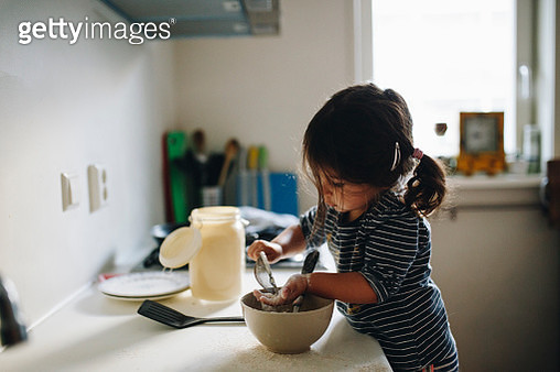 Side View Of Girl Preparing Food On Kitchen Counter At Home - gettyimageskorea