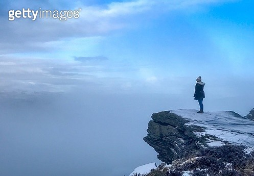 Side View Of Woman Standing On Cliff Against Cloudy Sky During Winter - gettyimageskorea