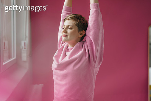 Woman in pink stretching at the window - gettyimageskorea