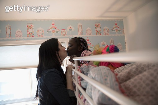 Affectionate mother kissing daughter waking in bunk bed - gettyimageskorea