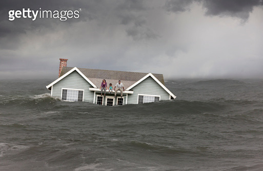 Family sitting on roof of house floating in sea - gettyimageskorea