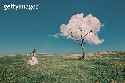 Dreamlike scenery with young girl and tree with a cloud - gettyimageskorea