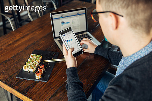 A man of the Millennial Generation is looking at his financial statement while eating lunch at a local sushi restaurant. He is using his bank's app on his smart phone and laptop to balance his monthly budget and plan for the future. Image taken in Utah, U - gettyimageskorea