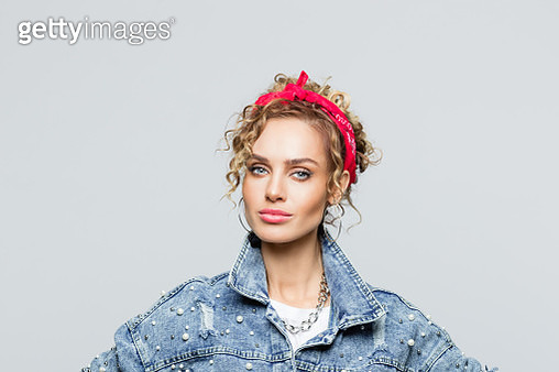 Portrait of blond curly hair confident young woman wearing white t-shirt, denim jacket and red bandana, looking at camera. Studio shot on grey background. - gettyimageskorea