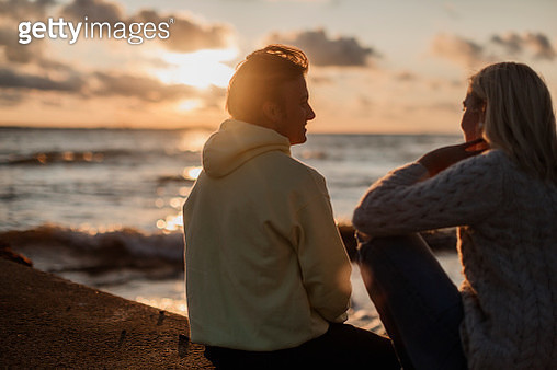 Couple sitting on beach at sunset - gettyimageskorea