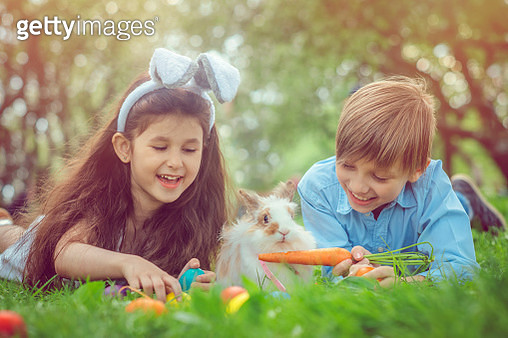 Happy children playing with bunny on Easter egg hunt - gettyimageskorea