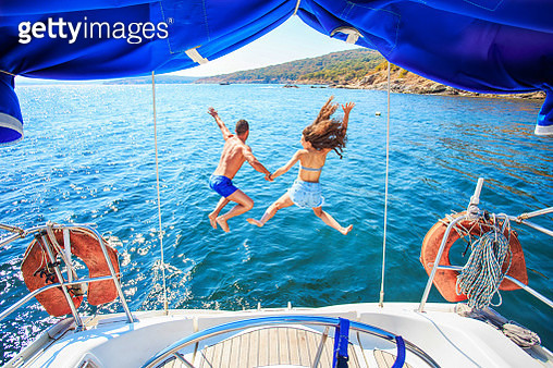 Rear view of couple jumping into ater - gettyimageskorea