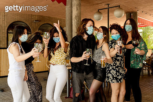 Young friends dancing while holding drinks at restaurant during coronavirus - gettyimageskorea