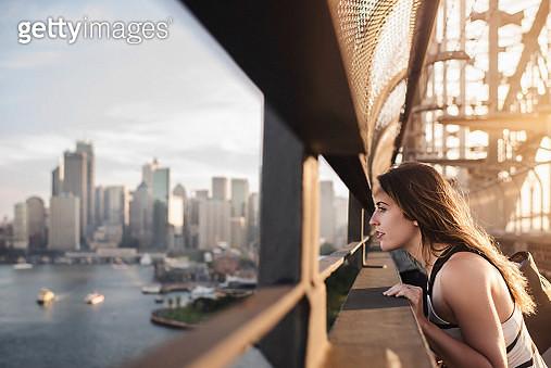 Beautiful woman looks out across modern city from steel bridge - gettyimageskorea
