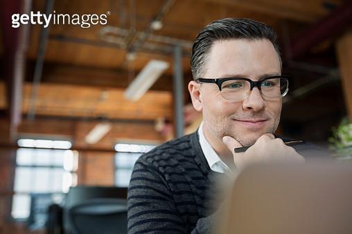 Smiling businessman working at laptop - gettyimageskorea