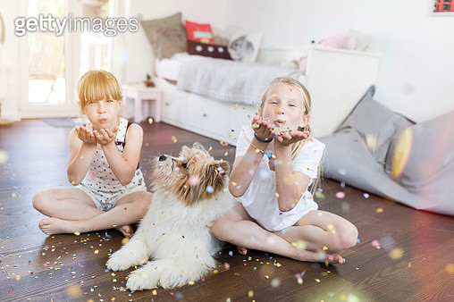 Two sisters with dog at home blowing confetti - gettyimageskorea