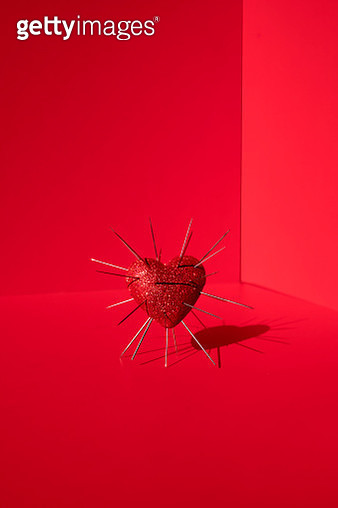 Shiny red heart shape with needles inserted on the red background - gettyimageskorea